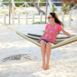Girl sitting in hammock on the beach - Stock Photo