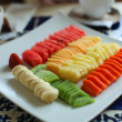 Exotic Fruit Dish with kiwi, banana, pineapple, strawberry, watermelon, papaya and melon - Stock Photo