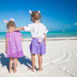Two little  cute girls in easter ears have fun on the exotic beach - Stock Photo