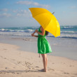 Royalty-Free Stock Photo: Young woman with yellow umbrella on the beach