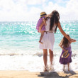 Mother and two kids at beach on sunny day - Stock Photo