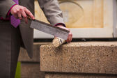 Groom cutting wooden log — Stock Photo