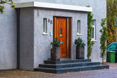 Neat entrance doorway with steps and pot plants — Stock Photo
