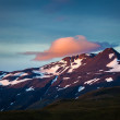 Stock Photo: Beautfiul pink cloud above snowy mountain peak