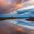 Stock Photo: Pink tinged clouds reflected in tranquil water