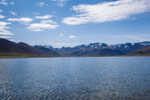 Snowy mountains with blue sky on a lake in Iceland — Stock Photo