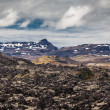 Stock Photo: Rocky landscape below volcanic mountains