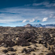 Rocky landscape below volcanic mountains — Stock Photo #39340613