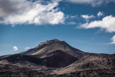 Rocky landscape below volcanic mountains — Stock Photo