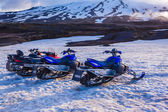 Four snow mobiles parked in thick winter snow — Stock Photo