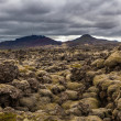 Rocky landscape below volcanic mountains — Stock Photo