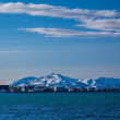 Stock Photo: Coastal town in Iceland with snow-capped mountains