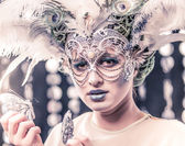 Young woman with venetian feather-mask — Stock Photo