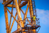 Worker climbing up a crane — Stockfoto