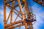 Worker climbing up a crane — Stock Photo