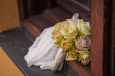 Wedding bouquet and bridal stola lying an a windowsill — Stock Photo