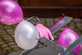 Pink and white balloons on a sawhorse — Stock Photo