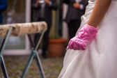 Bride wearing pink work gloves — Stock Photo