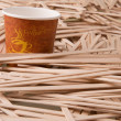 Wooden stirrers and paper coffee cup — Stok fotoğraf #46084377