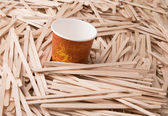 Wooden stirrers and paper coffee cup — Stock Photo