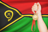 Medal in hand with flag on background - Vanuatu — Stock Photo