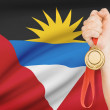 Stock Photo: Medal in hand with flag on background - Antiguand Barbuda