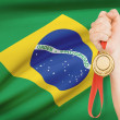 Medal in hand with flag on background - Federative Republic of Brazil — Stock Photo #41990741