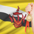 Stock Photo: Medal in hand with flag on background - Nation of Brunei, Abode of Peace