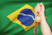 Medal in hand with flag on background - Federative Republic of Brazil — Stock Photo