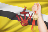 Medal in hand with flag on background - Nation of Brunei, Abode of Peace — Stock Photo
