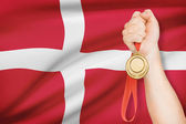 Medal in hand with flag on background - Kingdom of Denmark — Stock Photo