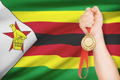 Medal in hand with flag on background - Republic of Zimbabwe — Stock Photo