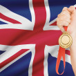 Medal in hand with flag on background - United Kingdom of Great Britain and Northern Ireland — Stock Photo #42613203