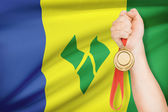 Medal in hand with flag on background - Saint Vincent and the Grenadines — Stock Photo