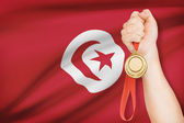 Medal in hand with flag on background - Tunisian Republic — Stock Photo