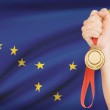 Medal in hand with flag on background - State of Alaska. Part of a series. — Stock Photo