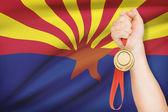 Medal in hand with flag on background - State of Arizona. Part of a series. — Photo