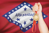 Medal in hand with flag on background - State of Arkansas. Part of a series. — Stock Photo