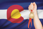Medal in hand with flag on background - State of Colorado. Part of a series. — Stock Photo