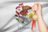 Medal in hand with flag on background - State of Illinois. Part of a series. — Stock Photo