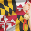 Medal in hand with flag on background - State of Maryland. Part of a series. — Stock Photo