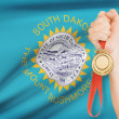 Medal in hand with flag on background - State of South Dakota. Part of a series. — Stock Photo #43454331
