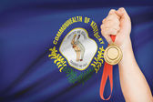 Medal in hand with flag on background - Commonwealth of Kentucky. Part of a series. — Stock Photo