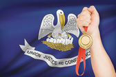 Medal in hand with flag on background - State of Louisiana. Part of a series. — Stock Photo