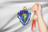 Medal in hand with flag on background - Commonwealth of Massachusetts. Part of a series. — Stock Photo