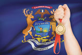 Medal in hand with flag on background - State of Michigan. Part of a series. — ストック写真