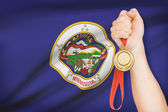 Medal in hand with flag on background - State of Minnesota. Part of a series. — Stock Photo