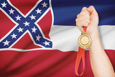 Medal in hand with flag on background - State of Mississippi. Part of a series. — Stock Photo