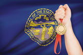 Medal in hand with flag on background - State of Nebraska. Part of a series. — Photo
