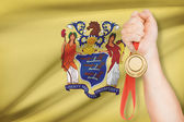 Medal in hand with flag on background - State of New Jersey. Part of a series. — Stock Photo